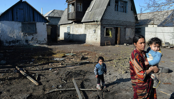 Женщина с детьми у дома, пострадавшего в результате артобстрела украинскими силовиками. Архивное фото