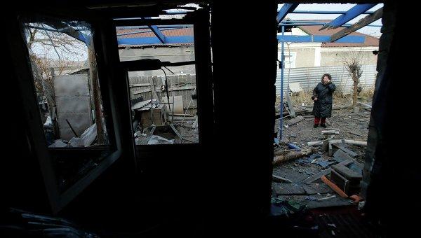 Женщина рядом с домом, поврежденным в результате обстрела поселка Красный пахарь