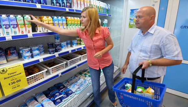 Покупатели у полки с молочной продукцией в магазине. Архив
