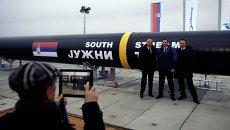 Люди фотографируются с частью газопровода Южный поток в Сербии