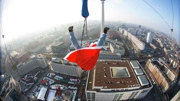 Мужчина в костюме Санта-Клауса в воздухе над Берлином