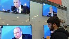 Мужчина смотрит телетрансляцию большой пресс-конференции президента России Владимира Путина в торговом центре города Грозного