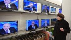 Посетительница магазина электроники в Москве смотрит телетрансляцию большой пресс-конференции президента России Владимира Путина