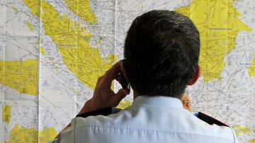Сотрудник аэропорта смотрит на карту Индонезии в кризисном центре, созданном для поиска пропавшего рейса QZ8501 компании Air Asia