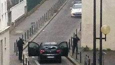 Вооруженные люди возле офиса издания Charlie Hebdo в Париже. Архивное фото