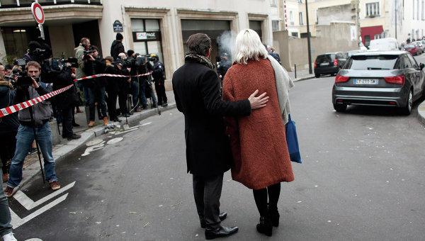 Люди стоят возле офиса издания Charlie Hebdo в Париже. Архивное фото