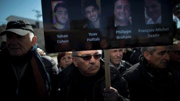 Мужчина держит плакат с портретами четырех жертв теракта в Париже