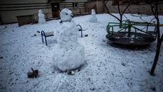 Снеговик на детской площадке, усыпанной осколками артиллерийских снарядов, после обстрела Донецка. Архивное фото