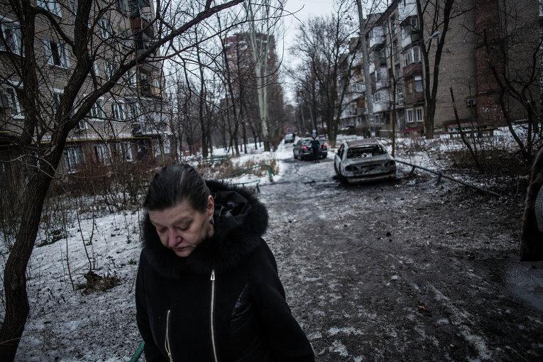 Женщина на улице в Донецке после обстрела украинскими силовиками