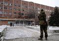 Вооруженный ополченец возле больницы, пострадавшей от обстрела ВСУ