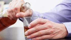 Мужчина держит бутылку с крепким алкоголем. Архив