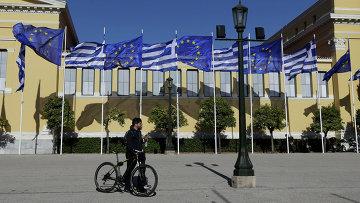 Мужчина с велосипедом на фоне флагов Греции и Евросоюза. Архивное фото