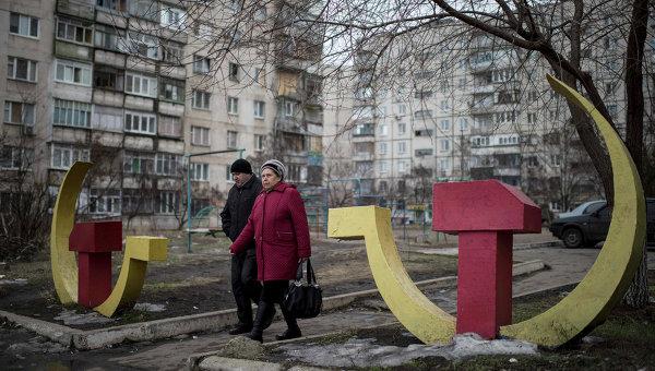 Местные жители проходят мимо скульптур серпа и молота в Мариуполе, Украина. Архивное фото