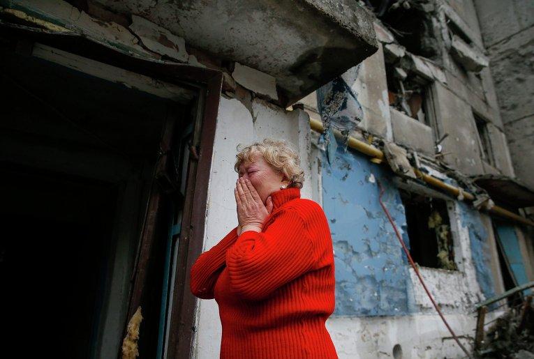 Женщина плачет возле разрушенного жилого дома в городе Енакиево