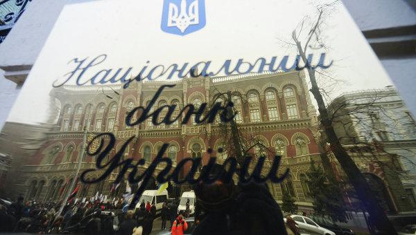 Вывеска Национального банка Украины с отражением активистов кредитного Майдана во время акции