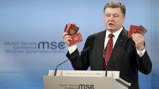 Президент Украины Петр Порошенко демонстрирует на Мюнхенской конференции паспорт и военный билет, которые якобы принадлежат российским военным. Архивное фото