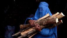 Афганская женщина несет купленные дрова в свой дом в Герате. Архивное фото