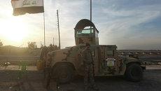 Солдат иракской армии стоит возле автомобиля. Архивное фото