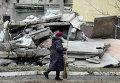 Женщина идет мимо разрушенного дома в Первомайске, Украина