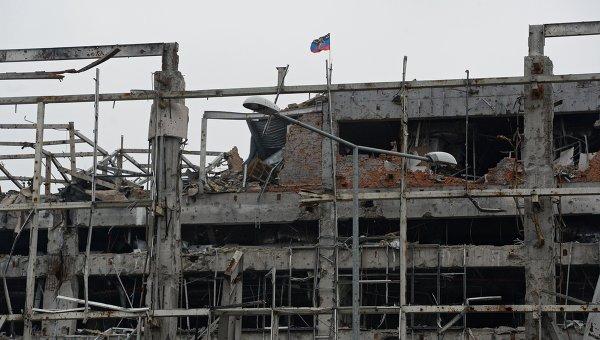 Флаг Донецкой народной республики над разрушенным зданием аэропорта города Донецка