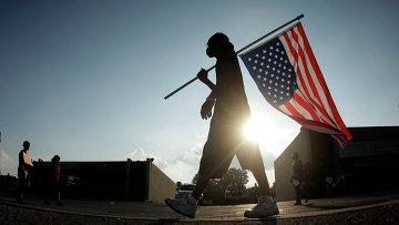 Человек с перевернутым американским флагом в городе Фергюсон, США. Архивное фото