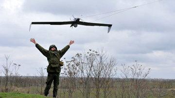 Российские военнослужащий запускает беспилотный летательный аппарат во время учений