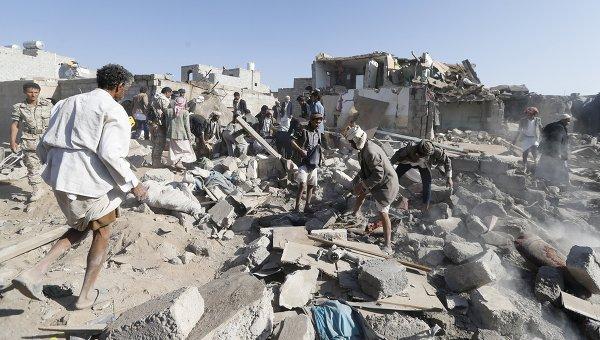 Люди разбирают обломки домов разрушенных при авиаударах вблизи аэропорта Саны