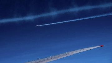 Вид из окна самолета на другой самолет, летящий в небе