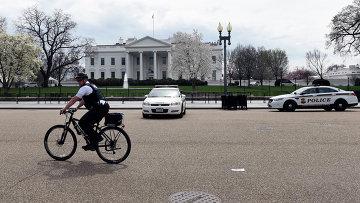 Сотрудник американских спецслужб на велосипеде перед зданием Белого дома в Вашингтоне