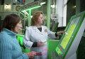 Сотрудница городской поликлиники № 64 помогает пациентке оформить талон на прием к врачу в терминале электронной очереди