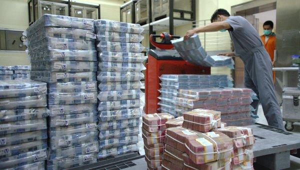 Сотрудники банка готовят денежные купюры для банкоматов и отделений в Джакарте, Индонезия. Архивное фото