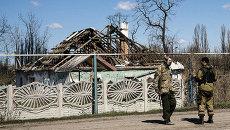 Ополченцы ДНР на фоне разрушенных построек в поселке Спартак в Донецкой области