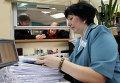 Сотрудница федеральной налоговой службы принимает заявления от налогоплательщиков