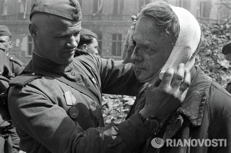 Советский солдат делает перевязку раненому в голову берлинцу