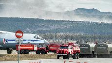 Пожарные автомашины и самолет ИЛ-76 МД во время подготовки для тушения лесных пожаров в Забайкальском крае. Архивное фото