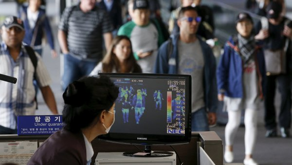 Пассажиры проходят мимо тепловизионной камеры в международном аэропорту Инчхон во время вспышки вируса MERS в Южной Корее