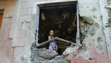 Девочка в пострадавшей квартире жилого дома, разрушенного в результате обстрела украинскими силовиками в Горловке