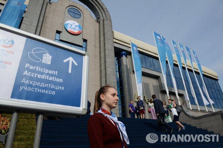 Волонтер у указателя к пункту аккредитации участников Петербургского международный экономического форума 2015