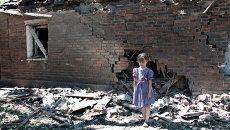 Девочка у дома, разрушенного в результате обстрела украинскими силовиками в Горловке. Архивное фото