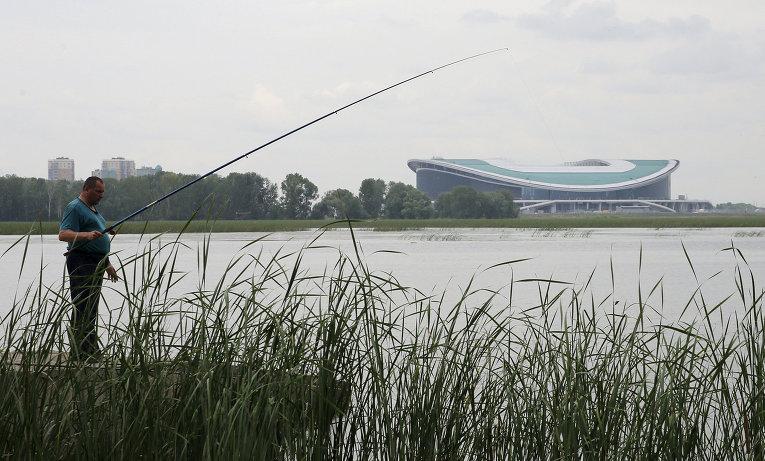 Мужчина рыбачит у стадиона Арена в Казани. Июль 2015