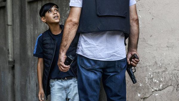 Турецкий полицейский задает вопросы курдскому мальчику после нападения на полицейских в городе Диярбакыр. Архивное фото