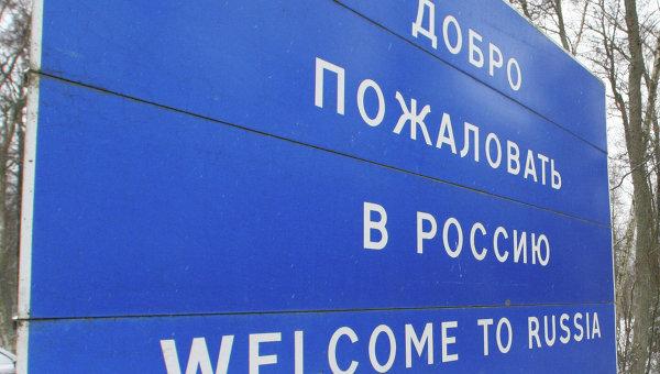 Пограничник у информационного щита Добро пожаловать в Россию. Архивное фото