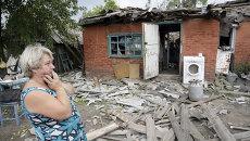 Женщина возле разрушенного во время обстрела дома в Донецке