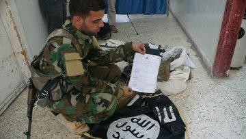 Сирийские военные досматривают оружие и вещи боевиков «Исламского государства», в том числе флаг ИГ. Архивное фото