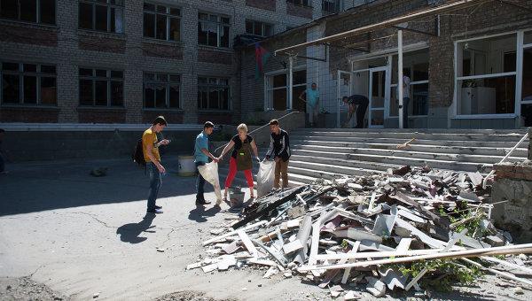 Жители Горловки убирают территорию школы № 16, пострадавшей от обстрела. Архивное фото