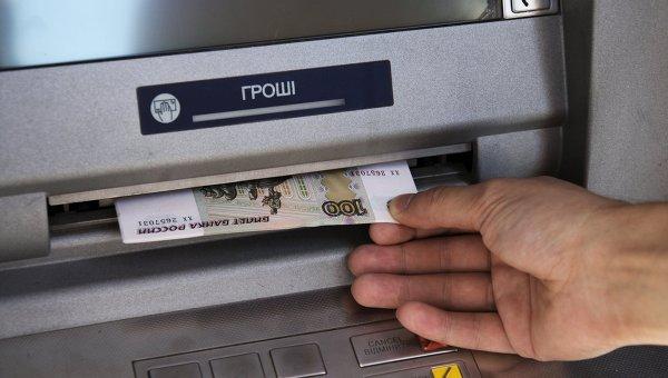 Горожанин обналичивает денежные средства в банкомате Донецка