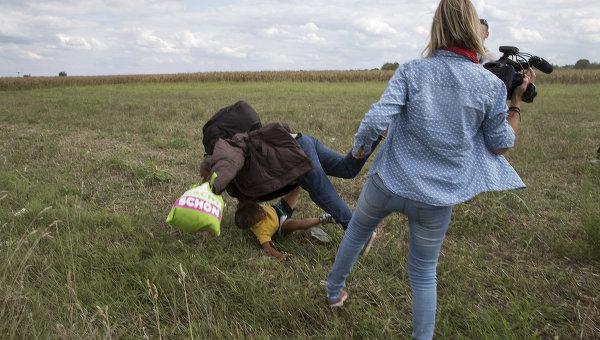 Журналистка телеканала N1TV во время съемки беженцев после побега из лагеря Реске на границе с Сербией. 9 сентября 2015
