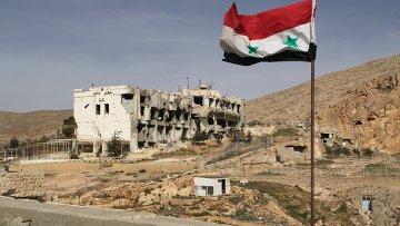 Сирийский флаг на фоне разрушенного дома в сирийском городе Маалюля в 55 км от Дамаска, который дважды захватывали и грабили боевики из группировки Джабхат ан-Нусра. Архивное фото