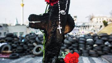 Обгоревшая доска, православный крест и цветы на баррикадах на Институтской улице в Киеве. Архивное фото