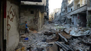 Местный житель на улице среди разрушенных зданий в районе Дахания в Дамаске. Архивное фото